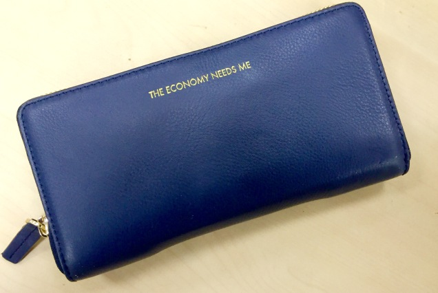 Photo of a blue ladies' purse with 'The Economy Needs Me' on it in gold lettering